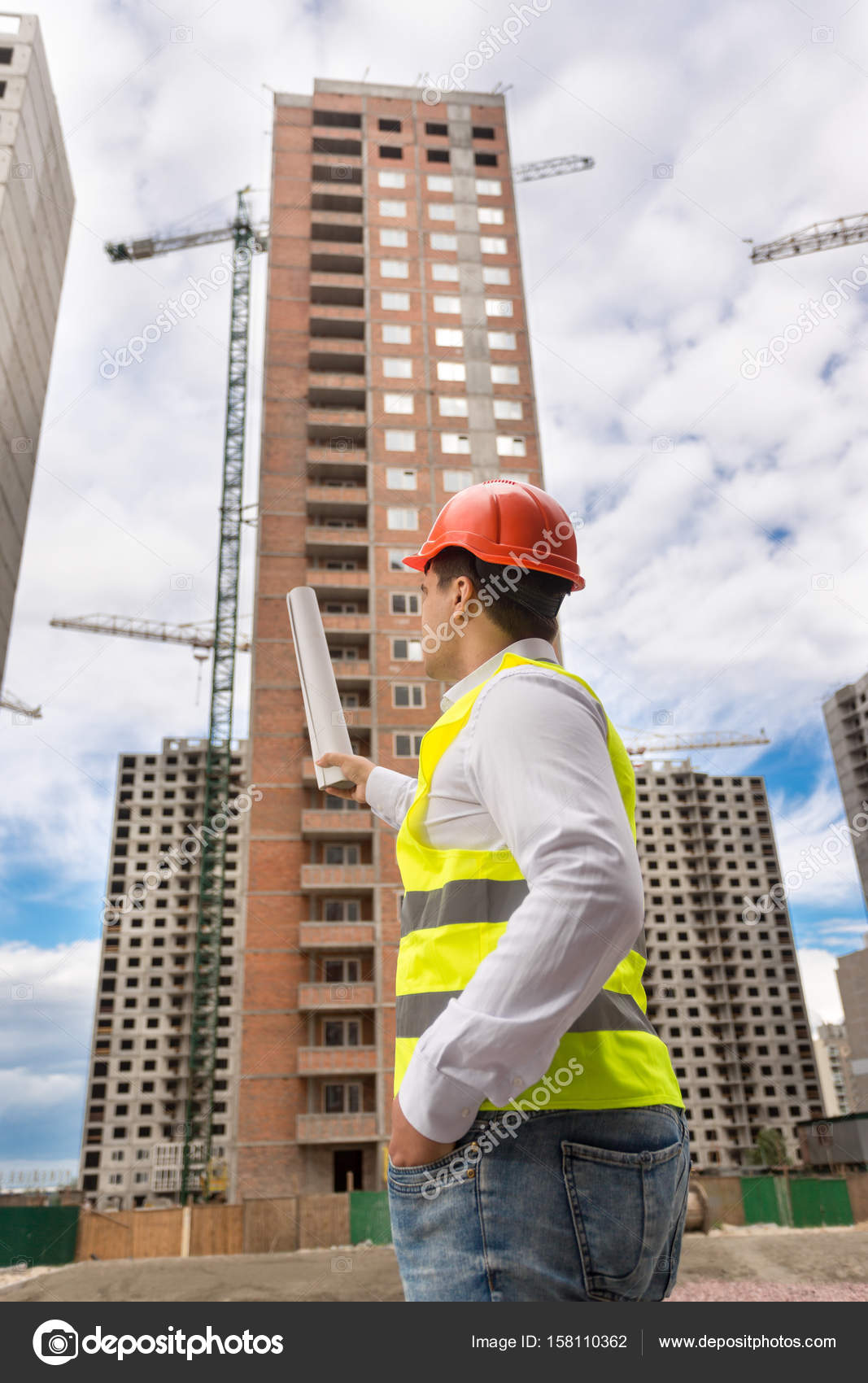 Rear view of architect pointing with blueprints at building unde rear view of architect pointing with blueprints at building unde stock photo malvernweather Images
