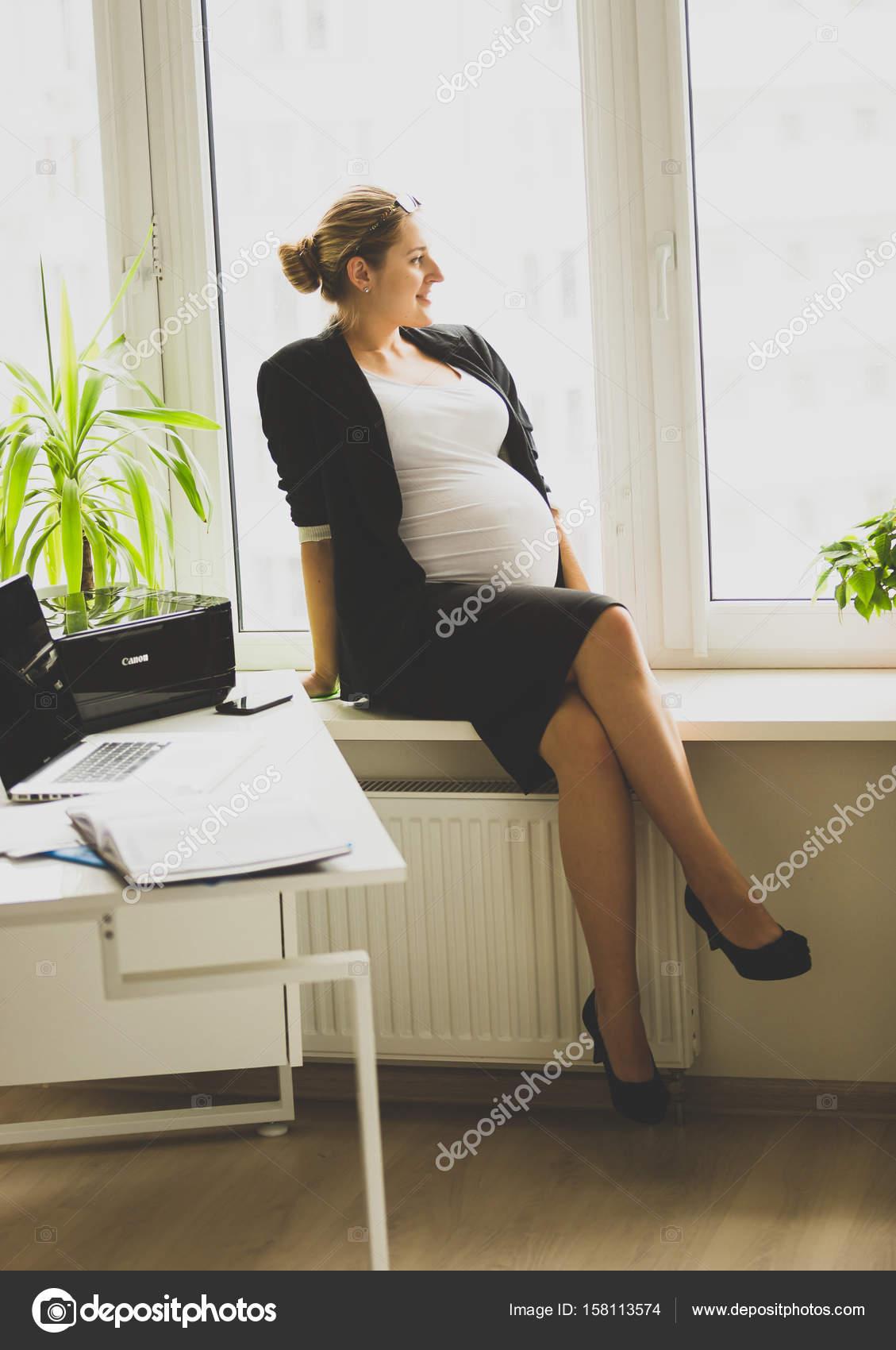 Junge Schwangere Geschaftsfrau Auf Der Fensterbank Sitzen Und Auf