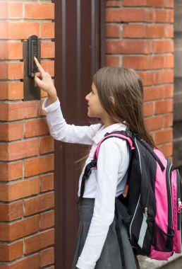 Cute schoolgirl in school uniform ringing in doorbell
