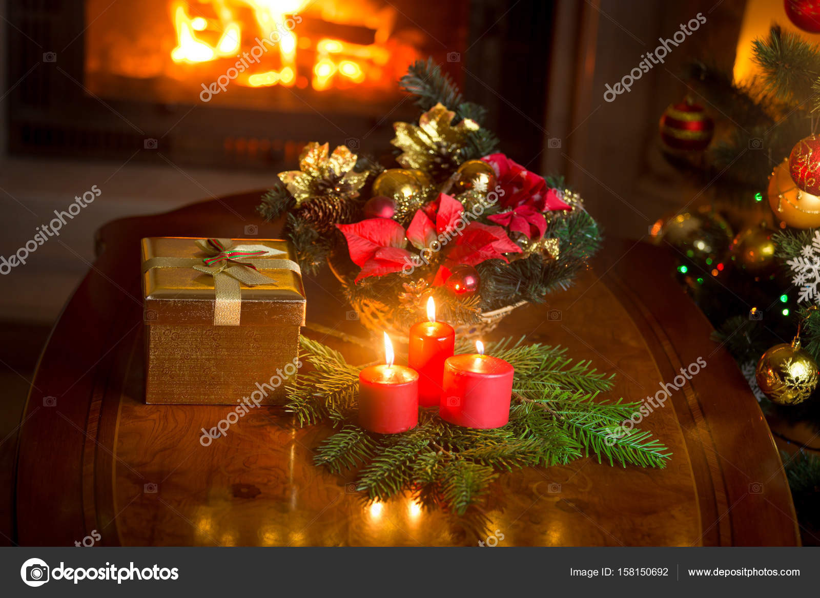 burning candles by the decorated christmas tree giftbox and tra stock photo