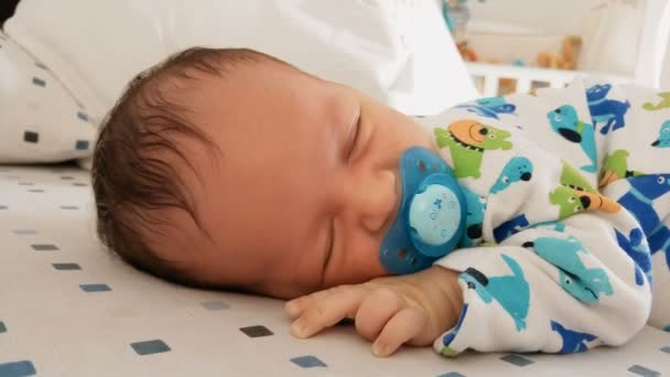 Portrait of cute newborn baby with soother sleeping in bed
