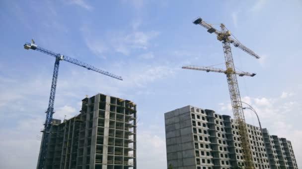 Moderní stavbě pracovní jeřáby na jasný slunečný den