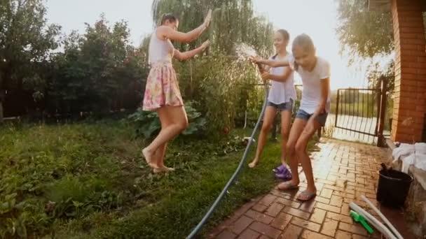 Slow-Motion-Video von glücklichen Kindern spritzt Wasser aus Gartenschlauch