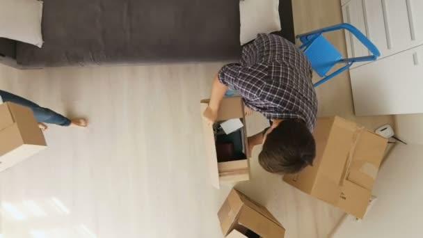 Pohled z vrcholu na mladé rodiny pohybující se v novém domě a rozbalování krabice