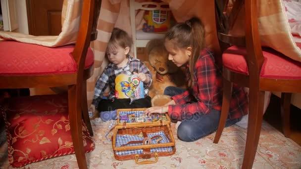 Neonato che gioca con la sorella in tenda fatta di coperte a living room