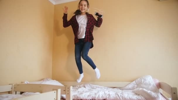 Slow motion video of cheerful teenage girl listening music with headphones and jumping on bed