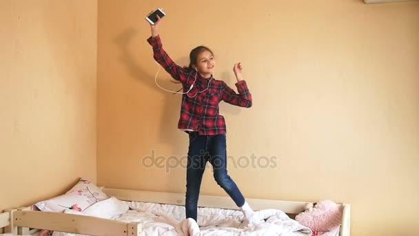 Slow motion záběry z Veselá dívka tančí na lůžku v ložnici