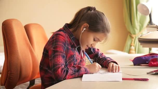 4k video of teenage girl listening music with earphones while doing homework at bedroom