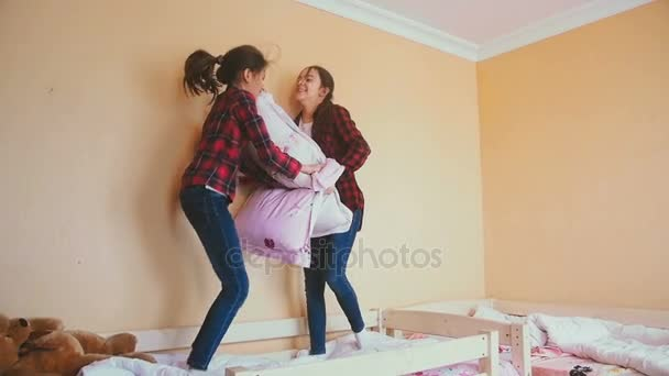 Two laughing girls jumping on bed and fighting with pillows