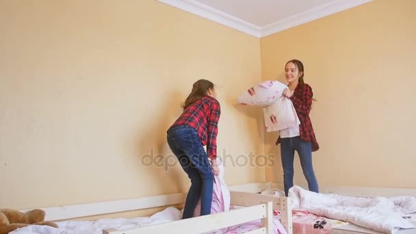 Slow motion footage of two teenage sisters fighting with pillows and laughing