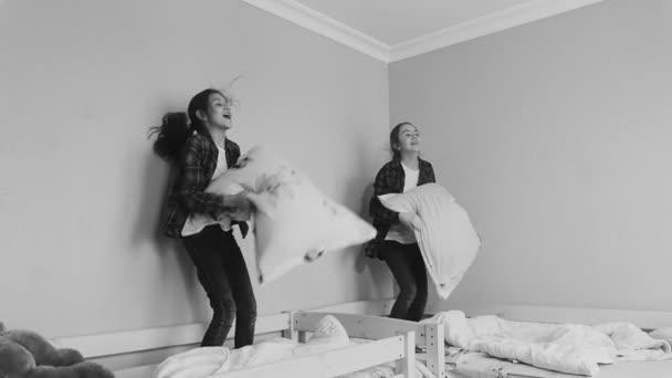 Fekete-fehér lassított felvételeket a két testvér, ugrás, párnák és ágynemű ágyban
