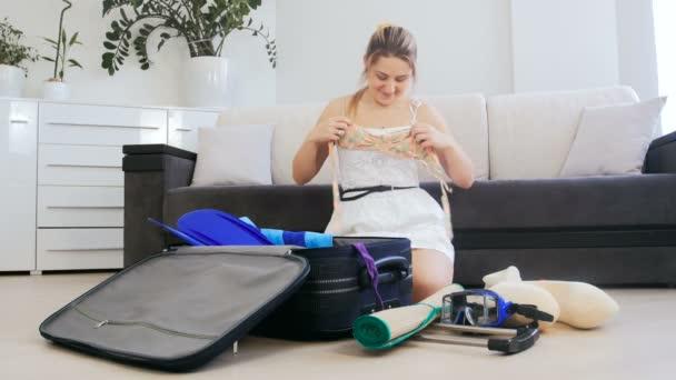 4 k záběry z mladá usmívající se žena sedí na podlaze v obývacím pokoji a cestovní kufřík pro letní dovolenou