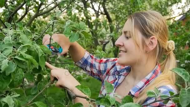 Portrét mladé usmívající se žena řezání větví na zahradu s nůžky