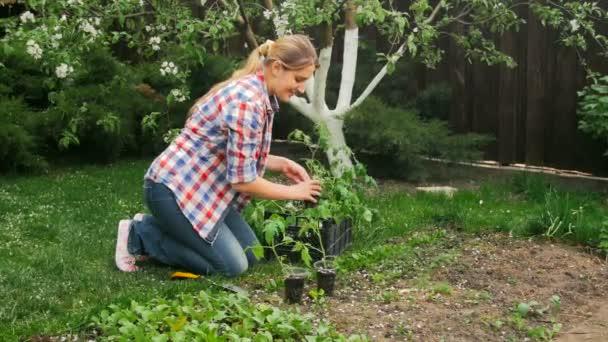Wunderschöne lächelnde Frau im Garten arbeiten und Tomate Sämlinge in den Töpfen aus großen Kiste herausnehmen