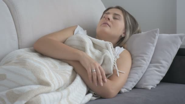Young woman suffering from headache lying on sofa and touching forehead. Footage shot at 4K resolution
