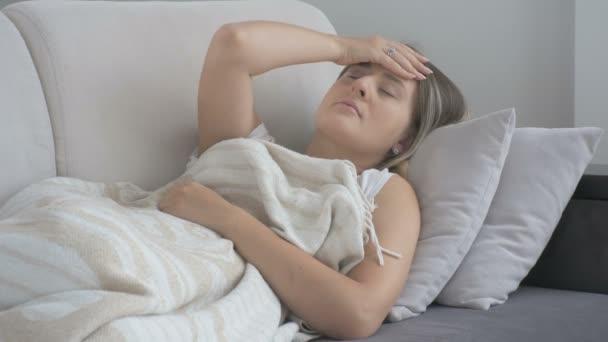unglückliche junge Frau mit Kopfschmerzen liegt Couch im Wohnzimmer. Aufnahmen in 4k