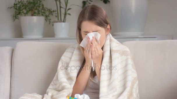 Junge kranke Frau auf Sofa sitzen und Nase im Taschentuch wehen