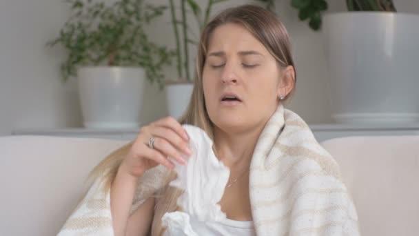 Detailní záběr mladé ženy trpící alergií na kýchání v papíru kapesník