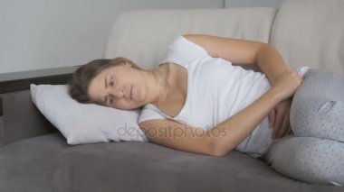 Young woman suffering from stomach ache lying on sofa at living room
