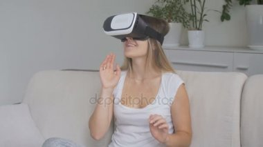 Young smiling woman wearing VR heeadset sitting on sofa at ling room. Concept of new technology. Footage shot in 4K