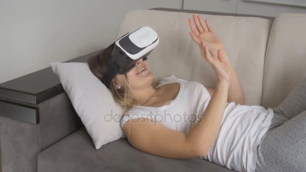 Fiatal mosolygó nő ágyon, és néz video 360 fokos Vr fejhallgató. 4 k felbontású felvételeket a lövés