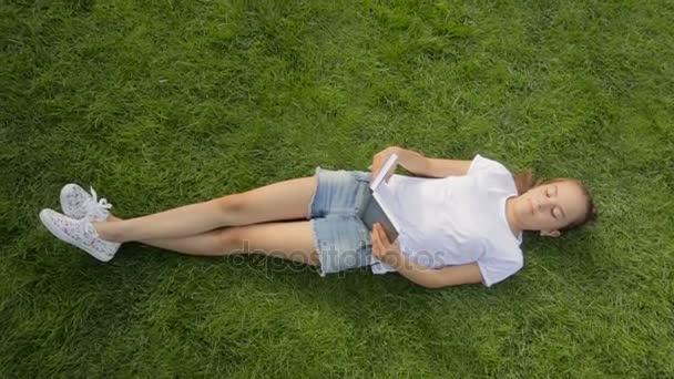Pohled shora záběr krásné usměvavé dívky relaxaci s knihou na trávě v parku