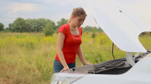 Young woman standing at broken car in field and looking under the hood