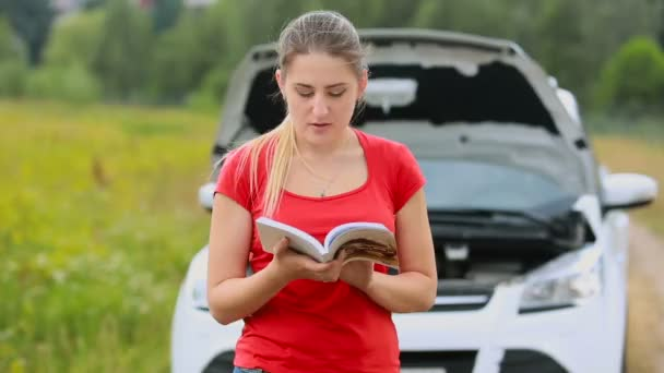 Young confused woman standing at brokedown car in the field and reading user manual