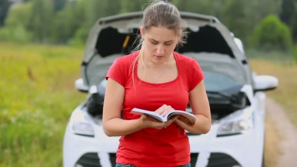 Upset young woman reading standing at brokedown car and reading manul on the deserted countryside road