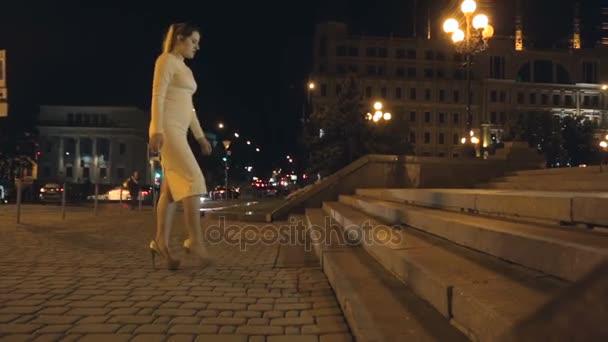 a085af55c Mujer sexy en vestido y tacones, subiendo las escaleras de piedra en la  calle por la noche