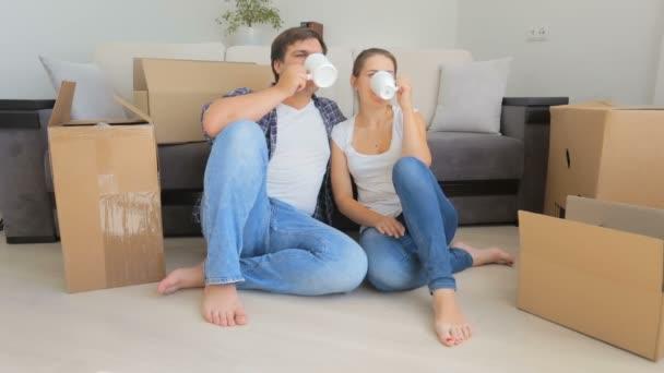 Šťastný mladý pár s přestávka na kávu při vybalování krabic v jejich novém domově