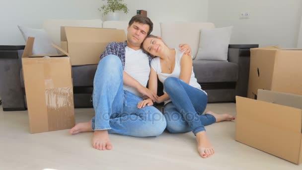Gyönyörű fiatal pár nyugszik padló után kicsomagolás dobozok, hogy új lakás