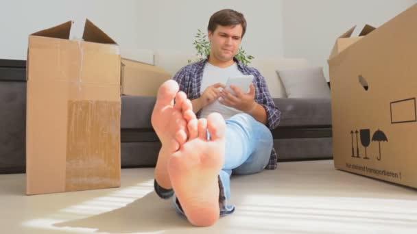 Dollly Shot von jungen Mann auf dem Boden sitzend, umgeben von Kartons und mit digitalem Tablet