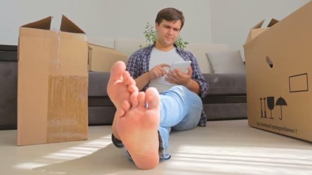 Dollly-Aufnahme eines jungen lächelnden Mannes, der in ein neues Haus zieht und ein digitales Tablet benutzt
