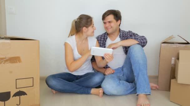 Šťastný mladý pár sedí na podlaze jejich nový byt a výběru nábytku na tabletu