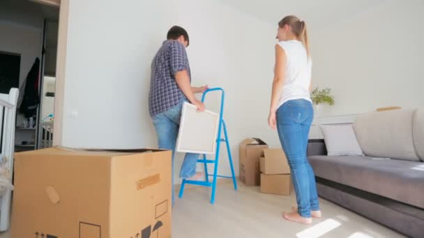 Young family moving to a new house and hanging painting on the wall