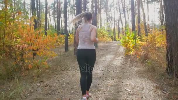 Slow motion of young slim woman jogging in park and running up the hill