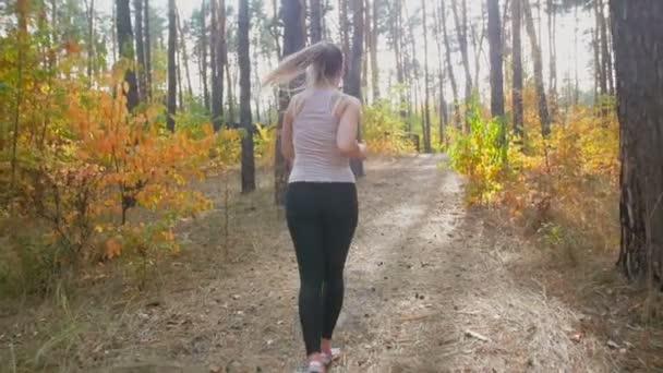 Zpomalený pohyb mladé štíhlé ženy běhání v parku a běh do kopce
