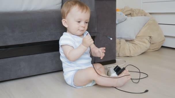 Konzept des Babys in Gefahr. Kleinkind spielt mit Drähten und Kabeln im Wohnzimmer