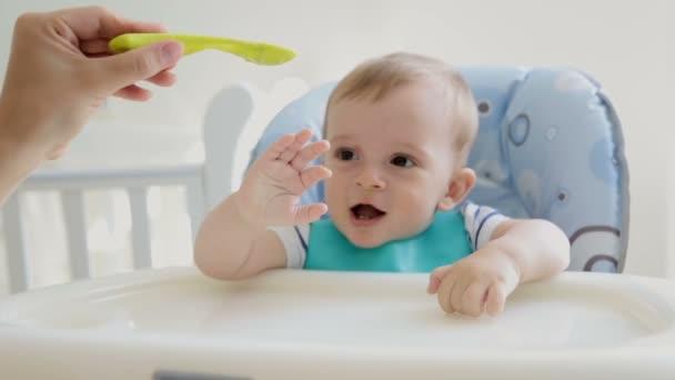 Veselý chlapeček baví a hrát zároveň jíst kaši v židličce