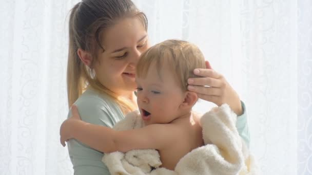 Portrait of beautiful young woman cuddling and kissing her baby son