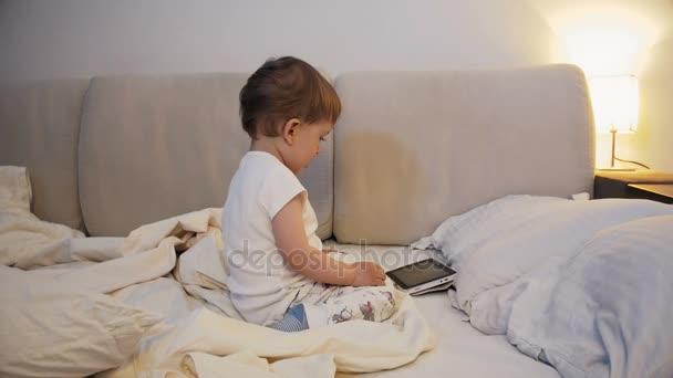 Bett Kleinkind Junge ~ Niedlichen kleinkind jungen am bett sitzen und zeichentrickfilme