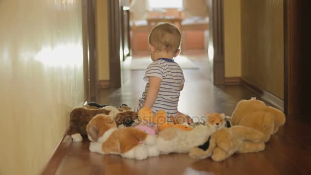Cute baby boy playing with stuffed animal toys on floor at home