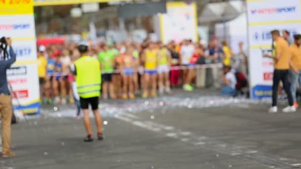 Skupina běžců stojí na startovní čáru a čeká na odpočítávání