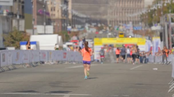 Rear view shot of  young woman running on city marathon day