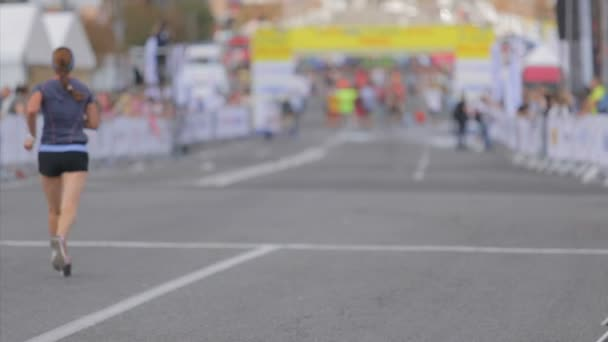Out of focus shot of runners going to the finish line at city marathon