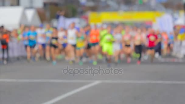 Large group of runners starting city marathon
