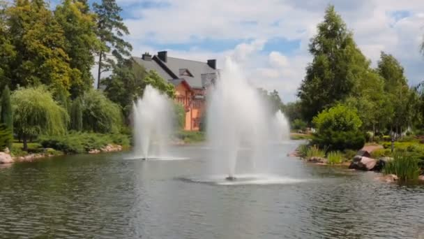Beautiful pond with fountains in front of luxurious mansion