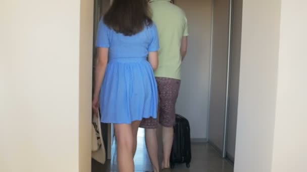 Šťastný mladý pár chůzi se zavazadly v hotelovém pokoji a objímání