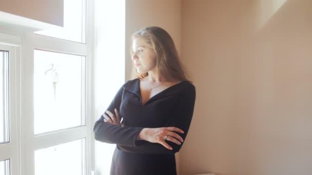 Mladý pohledný muž, objímání a líbání svou krásnou ženu na velké okno